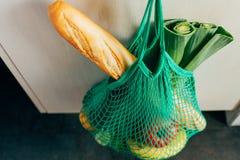 Panier vert de ficelle accrochant sur un crochet dans la cuisine photos libres de droits