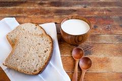 Panieren Sie Scheiben auf weißer Küchenserviette, einer hölzernen Schale Milch und t Stockbild
