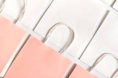 Panieres rosados en el fondo de los bolsos blancos aislados en el fondo blanco Foto de archivo libre de regalías
