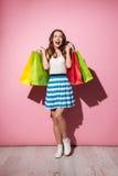 Paniers colorés de participation shopaholic enthousiaste heureuse de femme Image stock