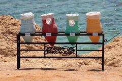Paniers colorés pour des recyclables devant la mer Photos libres de droits