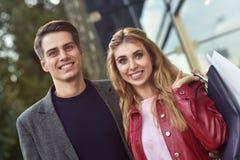 Paniers de transport de beaux jeunes couples affectueux et apprécier ensemble Décrivez montrer de jeunes achats de couples dans l photo libre de droits