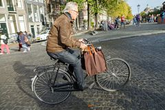 Paniers de transport d'un homme plus âgé sur le vélo Amsterdam, Hollandes Photo libre de droits
