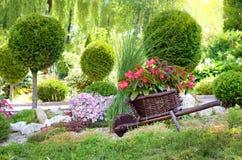 Paniers des fleurs sur un petit chariot un jour ensoleillé au printemps Photographie stock libre de droits