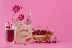 Paniers et jus de cerise sur le fond rose Photos stock