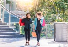 Paniers heureux de jeunes femmes à la boutique dans la ville Photos libres de droits