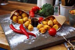 Panierte Kartoffelkroketten auf einer Holztischnahaufnahme Stockbild