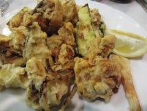 Paniertes und gebratenes knuspriges Gemüse mit Zitronenscheibe Zerschlagene Zwiebelringe, Zucchini, Kartoffeln und Blumenkohle It Stockbilder