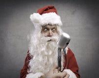 In Panik versetzte Santa Claus, die ein Mikrofon hält lizenzfreies stockbild