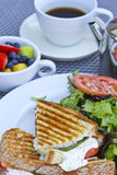 Panini Breakfast. With complimenting fruits and tea on white plates Royalty Free Stock Images