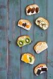 Panini con formaggio cremoso e frutta fresca su un fondo di legno rustico verde, struttura verticale Vista superiore, spazio per  fotografia stock
