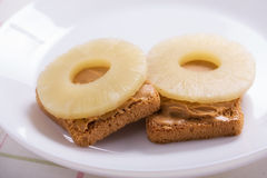 Panini con i cerchi dell'ananas e del burro di arachidi Immagini Stock