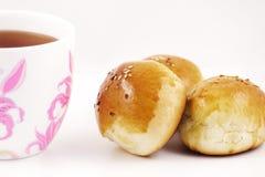 Panini con i semi di sesamo e una tazza di tè nero Immagine Stock Libera da Diritti