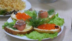 Panini con il pesce rosso e caviale ed aneto rossi su una lamiera e sui lamierini di insalata Tavolo da pranzo festivo alimento d video d archivio