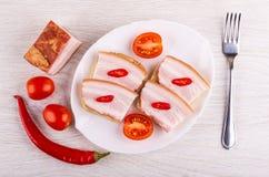 Panini con il petto, peperoncino, pomodoro in piatto, ciliegia del pomodoro, forcella sulla tavola Vista superiore immagine stock