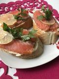 Panini con il salmone, decorato con i verdi ed il limone Trovi su un piatto su un tovagliolo rosso Immagini Stock