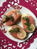 Panini con il salmone, decorato con i verdi ed il limone Trovi su un piatto su un tovagliolo rosso Immagine Stock Libera da Diritti