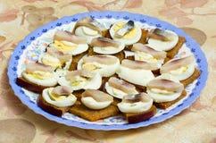 Panini con l'uovo ed i pesci su una zolla Immagini Stock