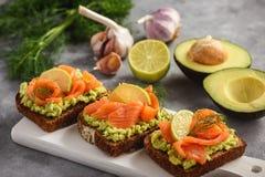 Panini con la diffusione ed il salmone affumicato dell'avocado immagini stock libere da diritti
