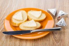 Panini con le fette di formaggio fuso in piatto, coltello Immagine Stock