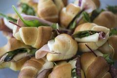 Panini del croissant con il formaggio del prosciutto e l'insalata di razzo fotografia stock