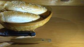 Panini del cursore e del sesamo sulla pagnotta affettata nel colpo panoramico di cestino del pane archivi video