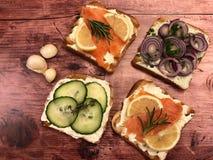 Panini del pane tostato con il formaggio cremoso, del salmone affumicato ed il cetriolo fotografia stock libera da diritti