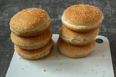 Panini dell'hamburger con i semi di sesamo su un tagliere immagine stock libera da diritti