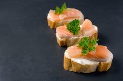 Panini di color salmone delle canape con le baguette sul fondo nero di lerciume Fotografia Stock