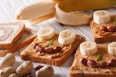 Panini divertenti con l'orizzontale della banana e del burro di arachidi Immagini Stock