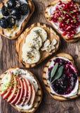 Panini dolci dell'assortimento con formaggio cremoso e la mela, melograno, inceppamento, uva, burro di arachidi, banana, seme di  Fotografie Stock Libere da Diritti