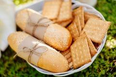Panini e biscotti sul piatto con il fondo dell'erba verde Fotografia Stock