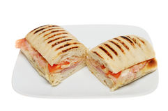 Panini. Ham, tomato and melted cheese panini on a plate isolated against white Stock Images