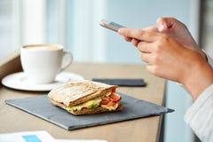 Panini kobieta z smartphone przy kawiarnią i kanapka Zdjęcia Stock