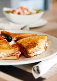 Panini Lunch. A plate with a delicious prosciutto panini with tomato, mozzarella cheese, olive and mayonnaise, served with a side salad Royalty Free Stock Images