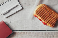 Panini with pen and notepad on office wooden table.  Royalty Free Stock Images