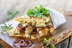 Panini with rosemary chicken. Toasted panini with grilled rosemary chicken breast fillet, melted mozzarella and roasted onion rings served on a wooden board Royalty Free Stock Images
