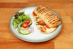 Panini and salad on a plate. On a wooden tabletop royalty free stock photos