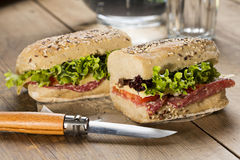 Panini sandwich. Image of a sandwich with red tomato, fresh lettuce and cheese, covered with sesame seeds wrapped in wrapping paper, on a wooden table with a Stock Image