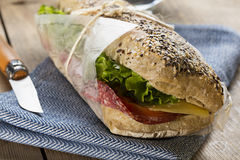Panini sandwich. Image of a sandwich with red tomato, fresh lettuce and cheese, covered with sesame seeds wrapped in wrapping paper, on a blue napkin with a Royalty Free Stock Photography