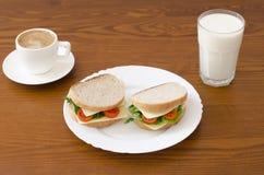 Panini su un piatto e su un bicchiere di latte, tazza di caffè su un fondo di legno Fotografia Stock Libera da Diritti