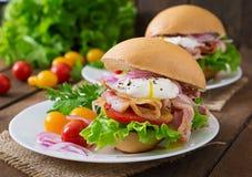 Panino con bacon e l'uovo affogato immagini stock libere da diritti