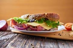 Panino con bacon, formaggio e le erbe su un piatto fotografie stock libere da diritti
