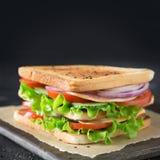 Panino con bacon, pomodoro, cipolla, insalata su fondo nero fotografia stock
