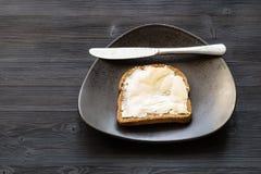 Panino con burro ed il coltello imburrati sul nero immagini stock libere da diritti