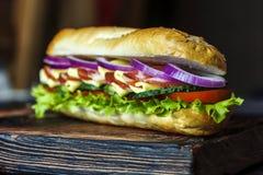 Panino con carne, la cipolla rossa, il formaggio, i cetrioli ed i pomodori su un bordo di legno Fotografie Stock Libere da Diritti