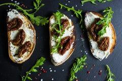 Panino con formaggio ed i pomodori secchi metà Immagini Stock