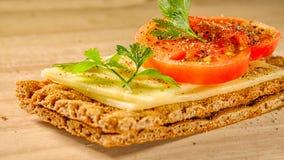 Panino con formaggio ed il pomodoro su pane asciutto squisito Fotografia Stock Libera da Diritti