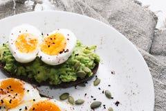 Panino con gli ortaggi freschi, l'avocado, gli uova sode ed i semi di zucca con olio d'oliva e pane Dieta sana o fotografie stock