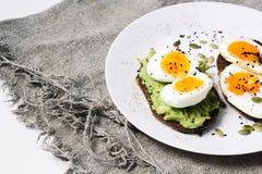 Panino con gli ortaggi freschi, l'avocado, gli uova sode ed i semi di zucca con olio d'oliva e pane Dieta sana o immagine stock